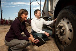 man and woman squatting down to look at semi truck wheel