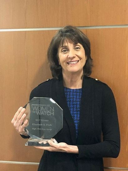 Image of Attorney Elizabeth Fitch holding Women to Watch Award